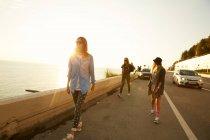 Друзья, ходьба на набережной — стоковое фото