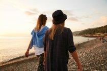 Девочки, ходить на каменистом пляже — стоковое фото