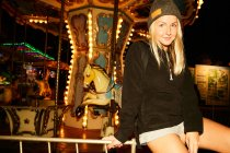 Girl sitting on carousel amusement park — Stock Photo