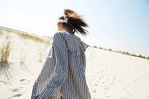 Mulher na viseira caminhando na praia — Fotografia de Stock
