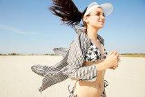 Mulher na viseira branca correndo na praia — Fotografia de Stock