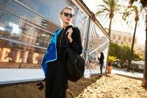 Красива жінка в сонцезахисні окуляри, ходьба з рушником на комунальних пляжу в Барселоні — стокове фото