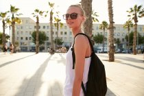 Blonde young tourist with black bag and sunglasses standing on street in barcelona — Stock Photo
