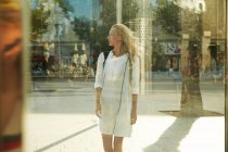 Young woman standing near glass on street in barcelona and looking away — Stock Photo