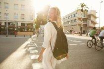 Jeune femme souriante marchant avec sac dans la rue à Barcelone — Photo de stock