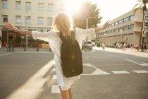 Visão traseira da mulher andando de braços abertos na rua em barcelona — Fotografia de Stock