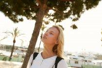 Atractiva mujer de pie en muelle en barcelona y mirando hacia arriba - foto de stock