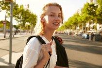 Fröhliche frau spaziert mit tasche auf straße in barcelona — Stockfoto
