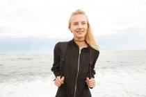Porträt einer schönen Frau in schwarzem Kleid und Tasche, die am Meer steht — Stockfoto