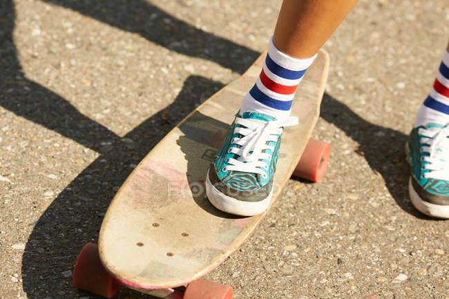 Jambes féminines en chaussettes avec planche à roulettes — Photo de stock