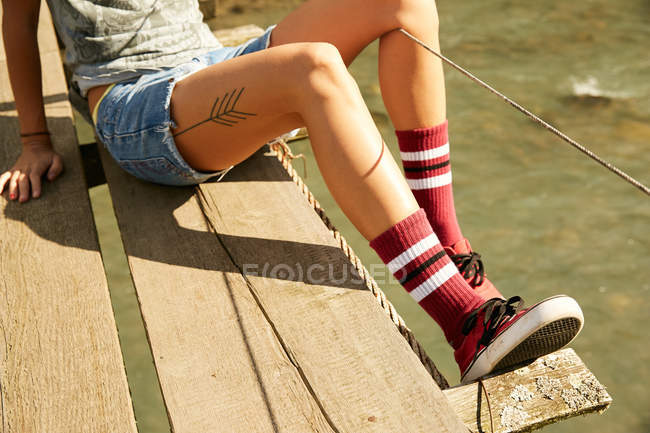 Female tattooed legs on footbridge — Stock Photo