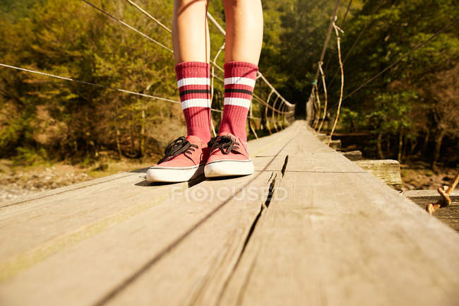 Female legs in knee socks and red sneakers — Stock Photo