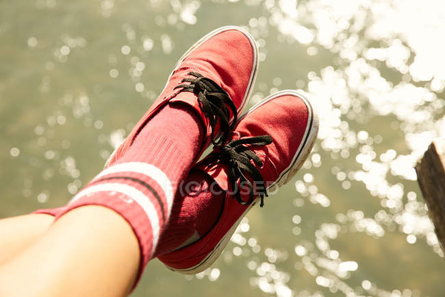 Female foots in knee socks and red sneakers — Stock Photo