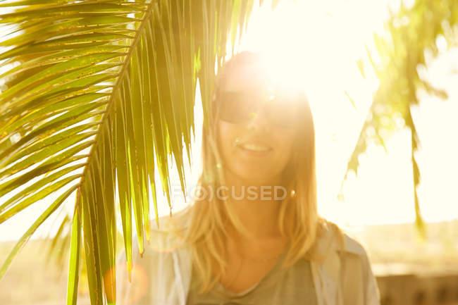 Женщина позирует на пляже с пальмой — стоковое фото