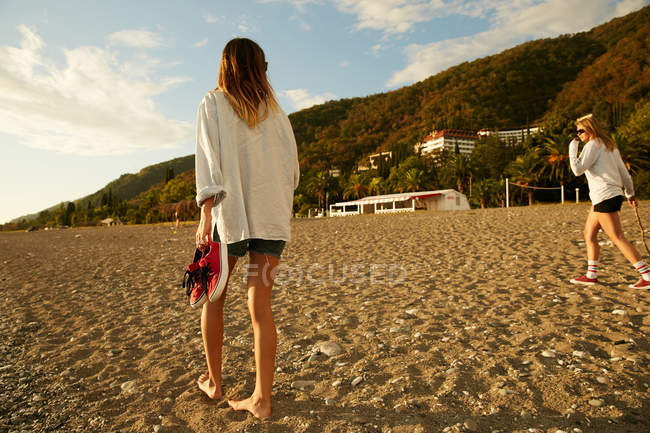 Woman walking on beach barefoot — Stock Photo