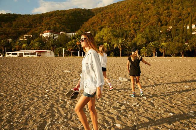 Femmes marchant sur la plage de vent — Photo de stock