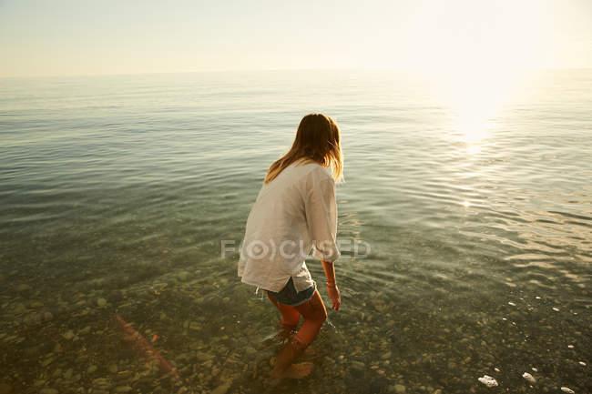 Mulher em pé na água na praia — Fotografia de Stock