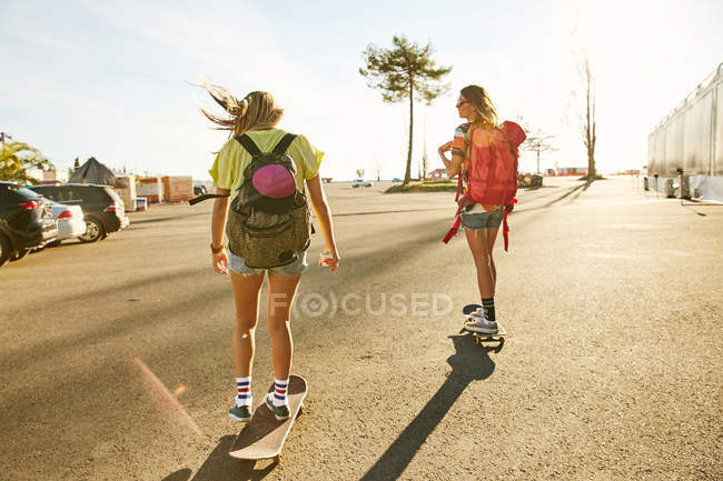Women riding on skateboards with backpacks — Stock Photo