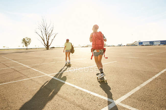 Women riding on skateboard with backpacks — Stock Photo