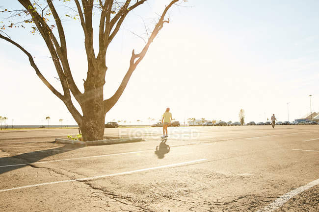 Woman riding on skateboard on parking lot — Stock Photo
