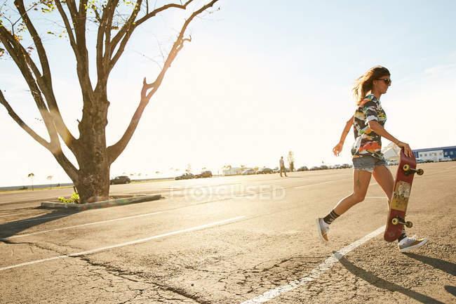 Woman riding on skateboard on parking lot — Stock Photo