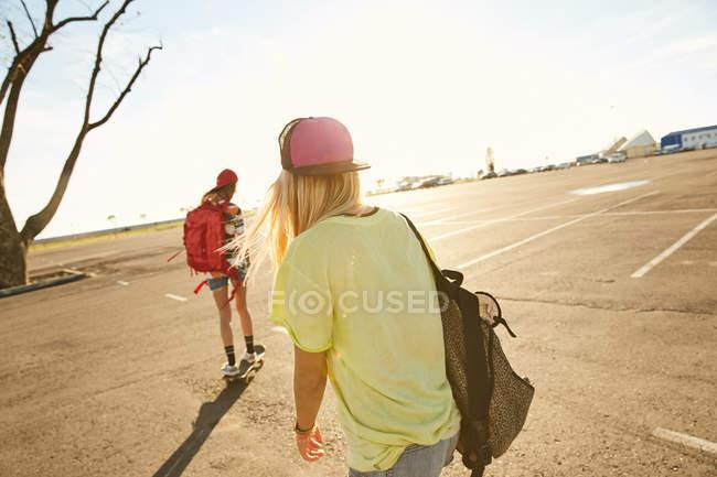 Femmes chevauchant sur skateboard avec des sacs à dos — Photo de stock
