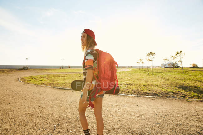 Woman walking with backpack and skateboard — Stock Photo