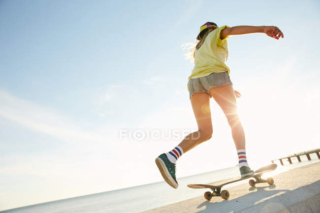 Femme chevauchant sur skateboard sur le bord de mer — Photo de stock