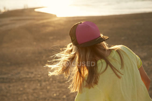 Woman in cap on windy beach — Stock Photo