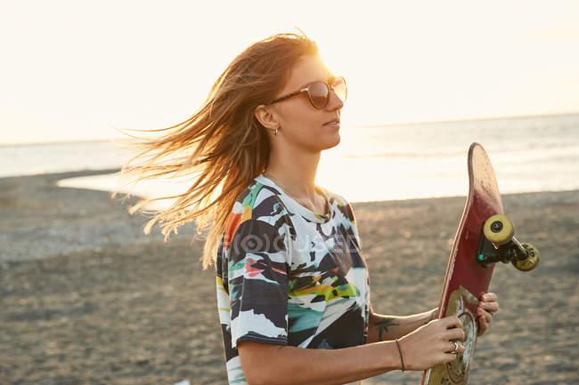 Femme tenant la planche à roulettes sur la plage — Photo de stock