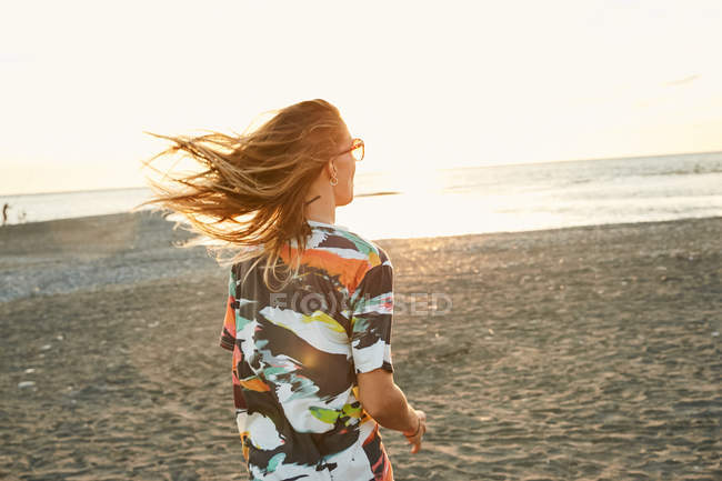 Femme qui marche sur la plage de vent — Photo de stock