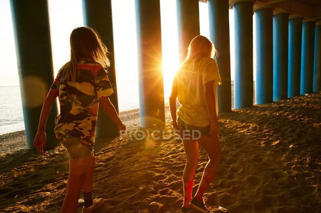 Mulheres andando na praia perto de colunas — Fotografia de Stock