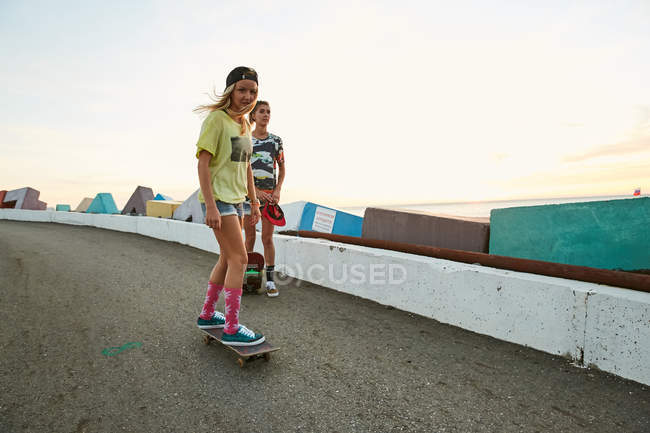 Women with skateboards on parking lot — Stock Photo