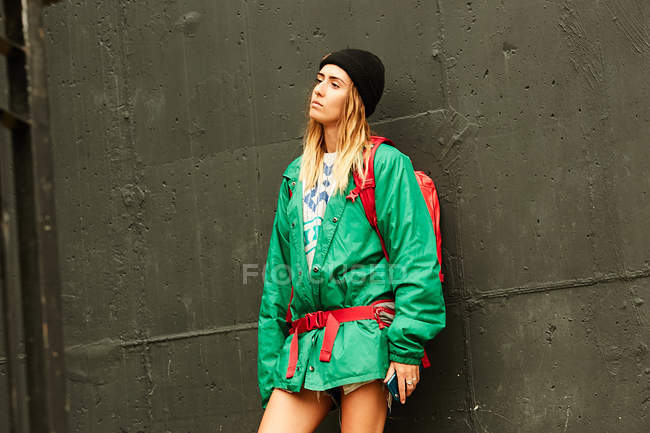 Woman in green jacket with backpack — Stock Photo