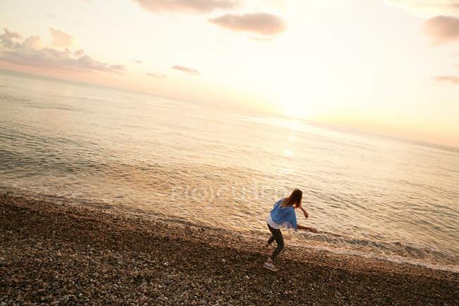 Fille jetant la pierre dans l'eau — Photo de stock