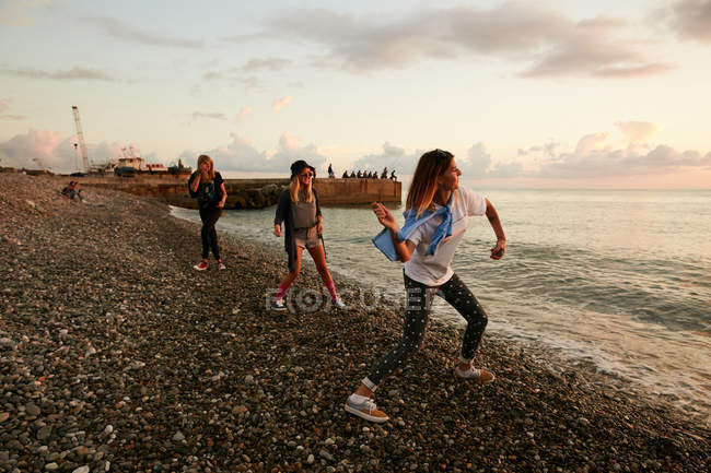 Friends throwing stones in water — Stock Photo