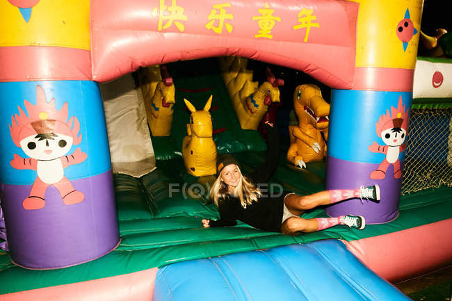 Girl having fun inflatable castle — Stock Photo