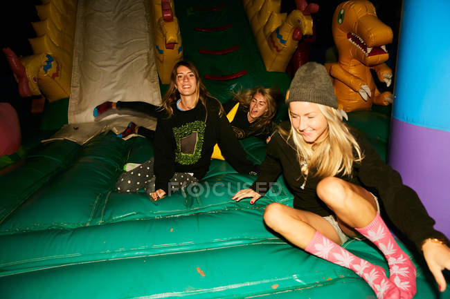 Friends having fun inflatable castle — Stock Photo