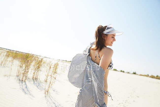 Woman in visor walking on beach — Stock Photo