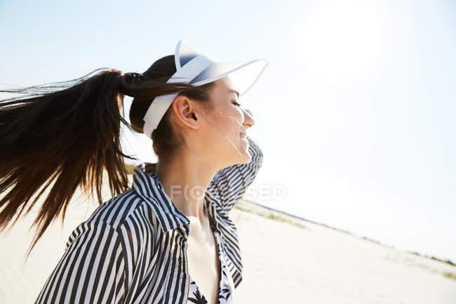 Жінка в білий козирок, насолоджуючись сонцем — стокове фото