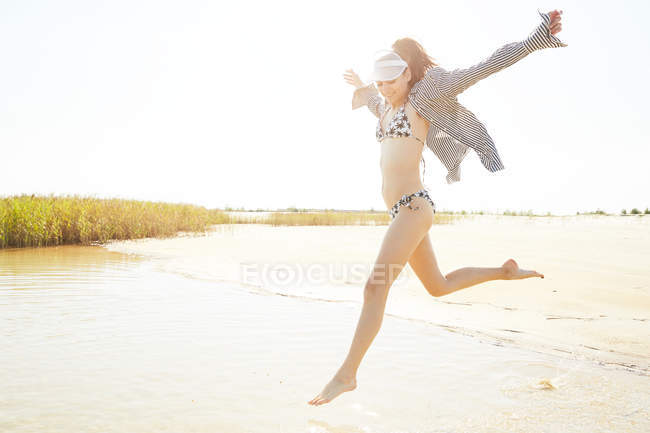 Woman in white visor jumping on beach — Stock Photo