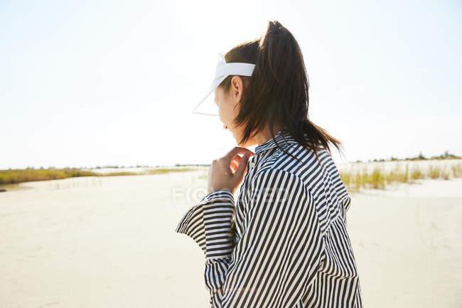 Mulher em branca viseira posando na praia — Fotografia de Stock