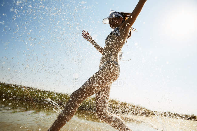 Woman in swimsuit running in water — Stock Photo