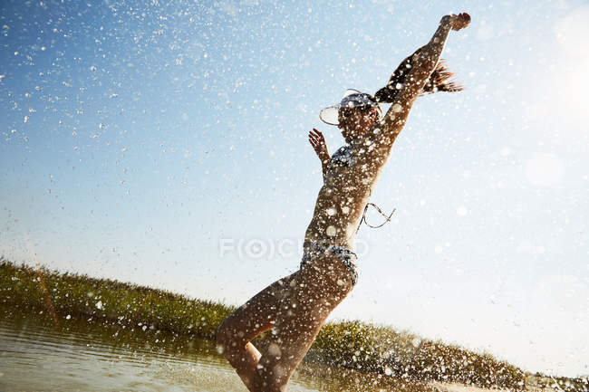 Woman in visor running into water — Stock Photo