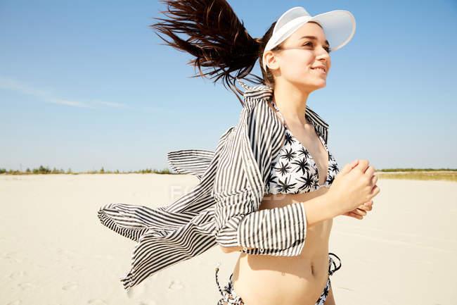 Woman in white visor running on beach — Stock Photo