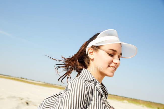Woman in white visor posing on beach — Stock Photo