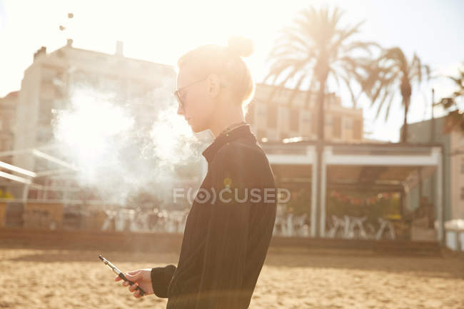 Side view of woman in sunglasses smoking electronic cigarette on beach in barcelona — Stock Photo