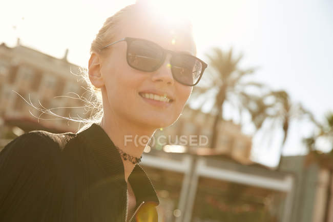 Portrait of smiling attractive woman in sunglasses standing on street at sunny day — Stock Photo