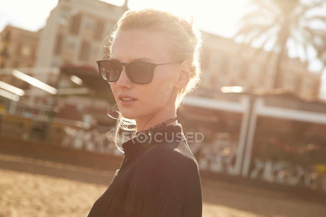 Портрет привлекательной женщины в солнечных очках, стоящей на улице в солнечный день — стоковое фото