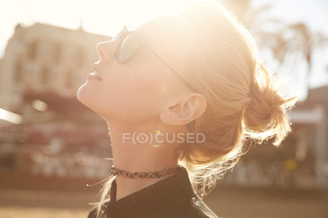 Side view of attractive woman in sunglasses standing on street at sunny day and looking up — Stock Photo
